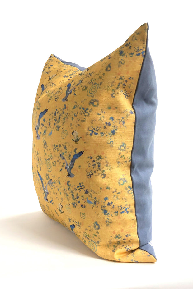 Decorative yellow throw pillow featuring an animal pattern design of birds in flight.