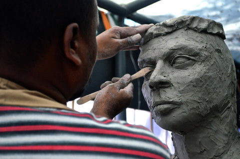 A Man Sculpting a Model of a Person