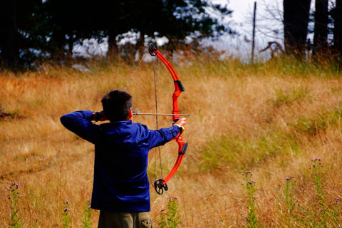 A young male shoots a compound bow in a field