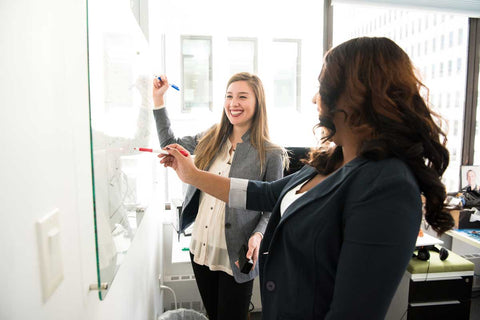 Women at work writing on a whiteboard and smiling