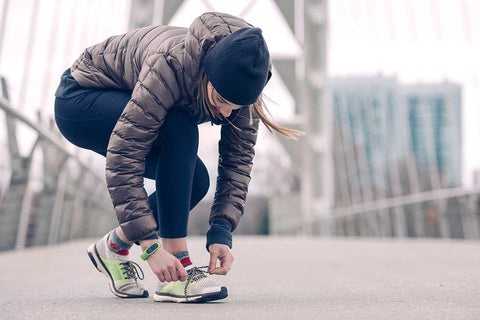 Jogging women tying her shoe