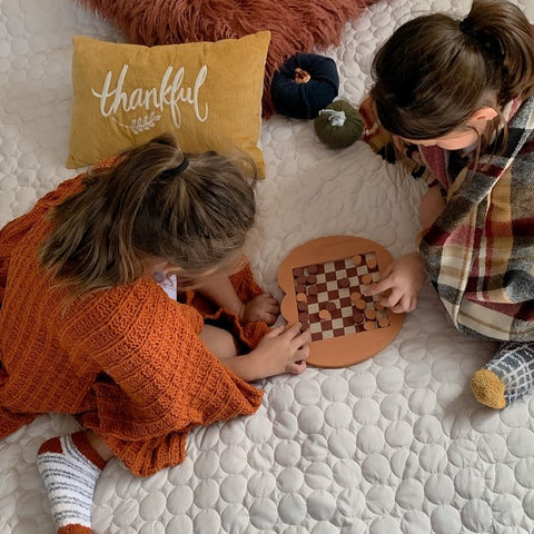 Little girls playing a board game with autumn decor on a circle quilt from Southshore Fine Linens