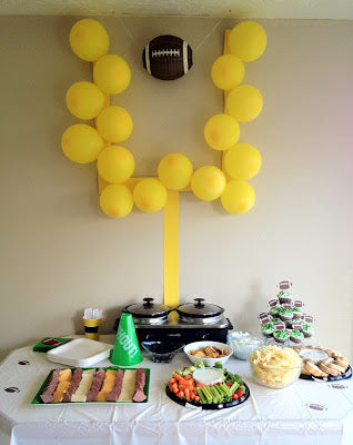 Football party decorations field goal made of balloons over table of appetizers