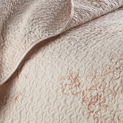 closeup of blush floral print pattern and embroidered detail of microfiber quilt set