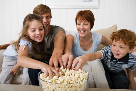 Family reaching for popcorn in unison