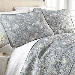 closeup of steel blue floral print quilted shams