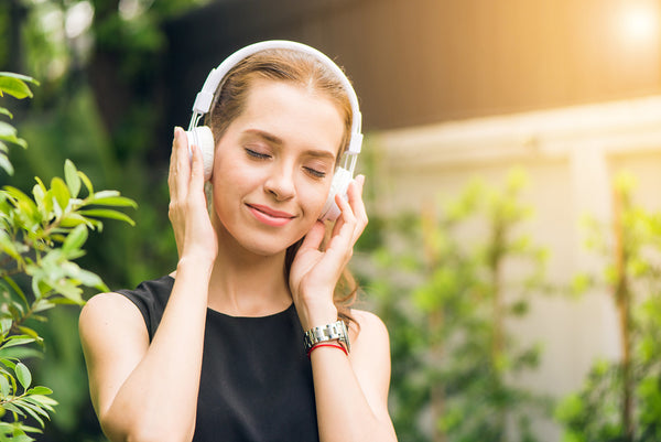 Woman listening to music through headphones
