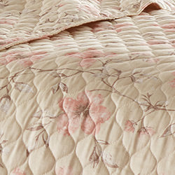 closeup of taupe grey floral print pattern of cotton quilt set