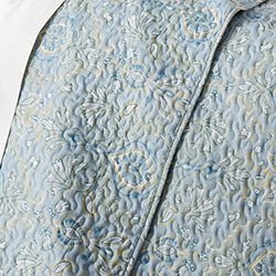 blue paisley print quilt pattern and sheet closeup
