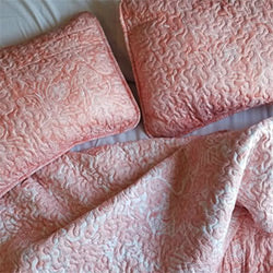 overhead view of pink paisley print quilt and sham set