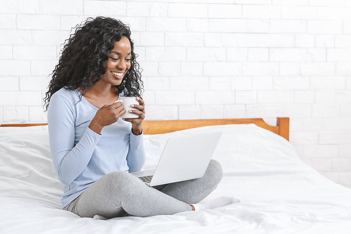 girl drinking coffee on bed