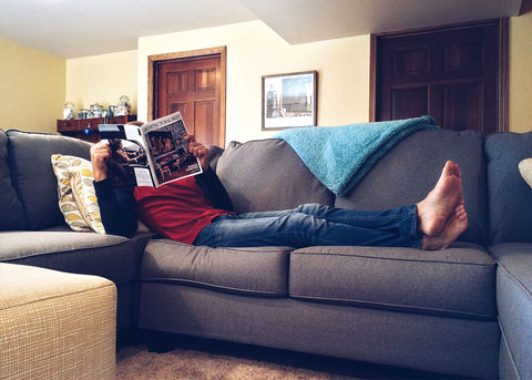 Man lounging on a sofa reading a magazine