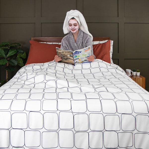 girl reading magazine in bed