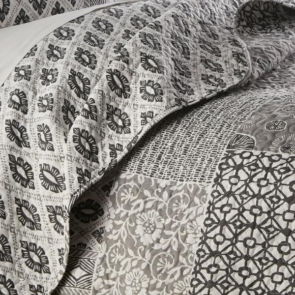 grey global patchwork quilt embroidered detail closeup