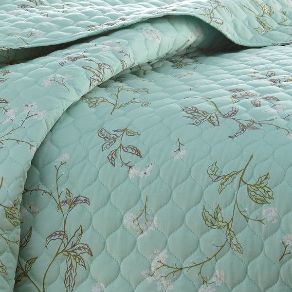 closeup of green floral print pattern and embroidered detail of cotton quilt set