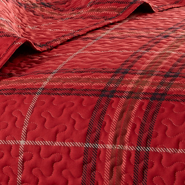 red plaid pattern quilt and embroidered detail stitching closeup