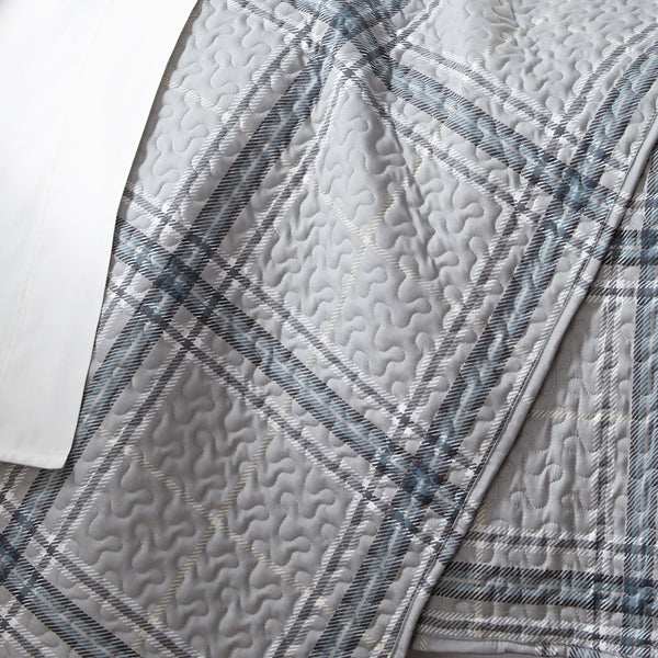grey and blue plaid print pattern and embroidered detail stitching closeup