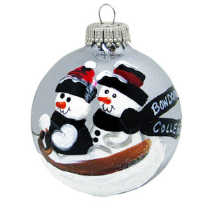 Silver glass ball ornament with two snowmen sledding. One has the words BOWDOIN COLLEGE on its scarf.