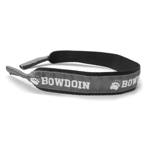 Black nylon webbing croakie with silver ribbon backing. Ribbon has repeating white imprint of paw prints alternating with BOWDOIN.