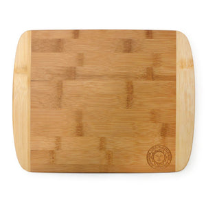 Bamboo cutting board with rounded corners. Light on the edges and dark in the middle. Engraved Bowdoin sun seal in lower right corner.