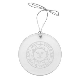 Round clear glass ornament with engraved Bowdoin sun seal and silver elastic hanging ribbon.