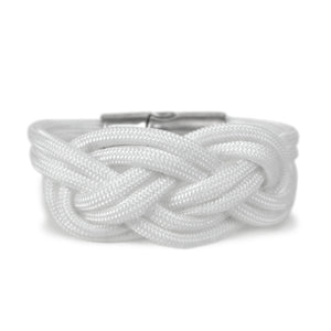 Bracelet made of white cord, tied in a double carrick knot.