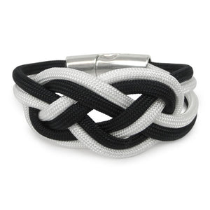 Bracelet made of black and white cord, tied in a double carrick knot.