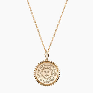 Small round pendant necklace with Bowdoin sun seal engraving, surrounded by sunburst edging.