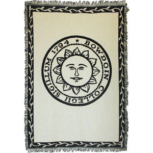 Ivory tapestry throw blanket with fringe. Black border with ivory vines. Large black imprint of Bowdoin sun seal in center.