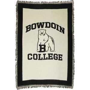Ivory tapestry throw with fringe and black border. Black woven imprint of BOWDOIN arched over polar bear mascot over COLLEGE.