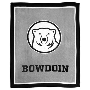 Knit blanket in grey with thin white inner border and thick black outer border. In the center of the blanket is a large knit-in Bowdoin mascot medallion over the word BOWDOIN.