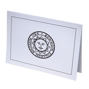 White notecard with sun seal on front.