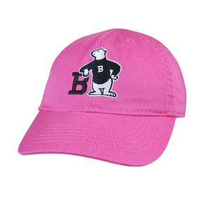 Pink twill hat with Spirit Bear embroidery: A polar bear wearing a black sweater with a white B on it, leaning with one elbow on the letter B and its other hand on its hip.