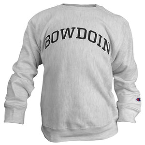 A photo of a children's crewneck sweatshirt in silver heather. There is a small Champion C logo patch in red white and blue on the left sleeve just above the cuff. The word BOWDOIN is imprinted in an arch across the chest in black with a white stroke outline.