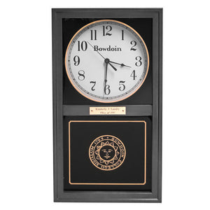 Black wall clock with white face and arabic numerals. Bowdoin wordmark on face of clock. Inset Bowdoin sun seal in gold below.