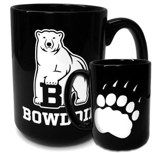Two sides of black coffee mug: one side has a white imprint of the polar bear mascot over the word BOWDOIN; the other side has a white paw print.
