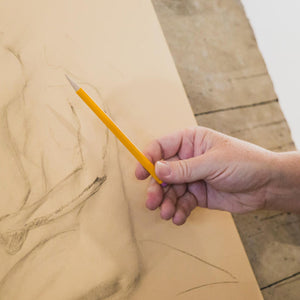 White man's hand doing a figure drawing with a yellow mechanical pencil.
