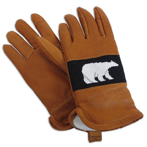 Photo of tan leather gloves with a needlepointed panel on the back of the hand depicting a white polar bear on a black background. The gloves have a plush white fleece lining and a pull-on tab at the wrist with the logo SMATHERS & BRANSON imprinted on the tab.