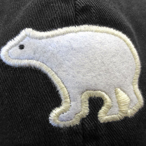 A closeup shot of the white felt polar bear embroidered in white on a black twill hat. The polar bear is in profile and has a small eye embroidered in black on its face.