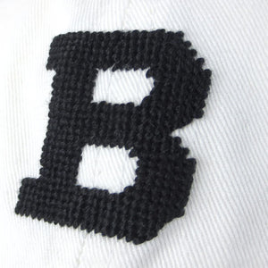 Closeup view of needlepointing on white hat.