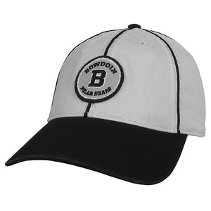 Silver-gray twill ball cap with black bill and ribs. Circular gray patch with black embroidery. There's an embroidered white stroke inside the border of the patch and around the solitary letter B.