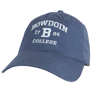 Slate blue baseball hat with white embroidery of arched BOWDOIN over 17 B 94 over COLLEGE.