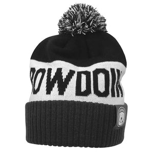 Knit cuffed pom beanie with charcoal cuff, white middle, and black top, with grey, black, and white pom. Knit in BOWDOIN in black on white band. Small fabric tab with Bowdoin mascot medallion on cuff.