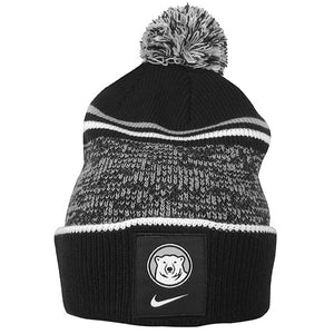 Black knit beanie with black, white, and grey pom. Grey and white stripes and wide band of marled black and grey. Patch on cuff of Bowdoin mascot medallion with a Nike Swoosh beneath.
