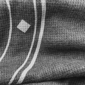 Closeup showing texture of waffle-knit fabric and screen imprint.