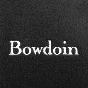 A closeup of black fleece with the word BOWDOIN embroidered on it in white.