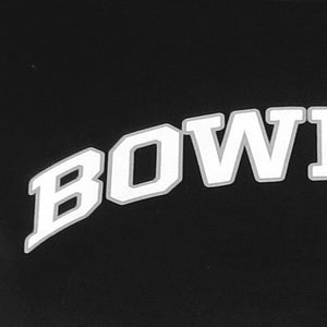 Closeup of BOWDOIN imprint on women's Nike Legend tee, showing black fabric and letters imprinted in white with grey outline.