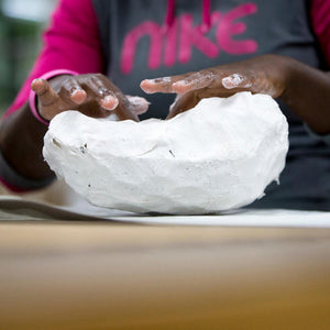 Black woman's hands shaping a white plaster scuplture.