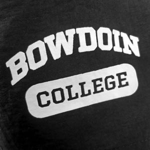 Closeup of imprint of BOWDOIN in white arched over COLLEGE inside a white cartouche.
