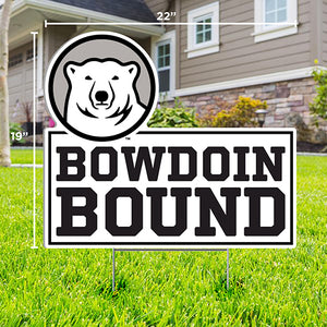 Lawn sign with cutout of mascot medallion over text BOWDOIN BOUND staked in a grassy lawn in front of a house.